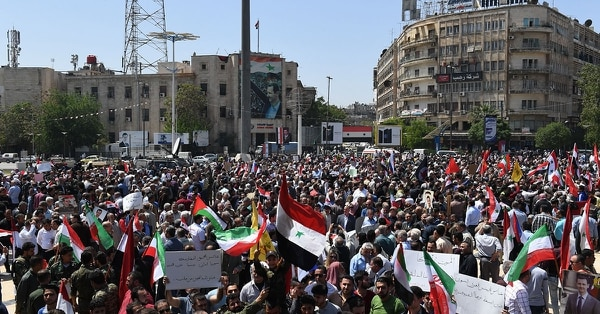 Syrians wave the national flag and portraits of President Bashar al-Assad as they gather in Aleppo's Saadallah al-Jabiri square on April 14, 2018, to condemn the strikes carried out by the United States, Britain and France against the Syrian regime. (George Ourfalian/AFP/Getty Images)