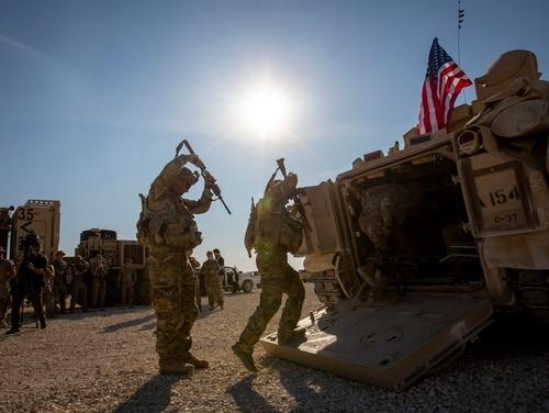 Crewmen enter Bradley fighting vehicles at a U.S. military base at an undisclosed location in northeastern Syria, Monday, Nov. 11, 2019. (Darko Bandic/AP)