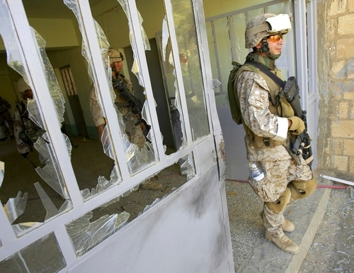 This file photo from Aug. 6, 2005, shows U.S. Marine Staff Sgt. Brian Hamilton of Columbus, Ohio, from Lima Company of the 3rd Battalion, 25th Regiment as he exits after searching a school, in Parwana, near Haditha, Iraq. (Jacob Silberberg/AP)