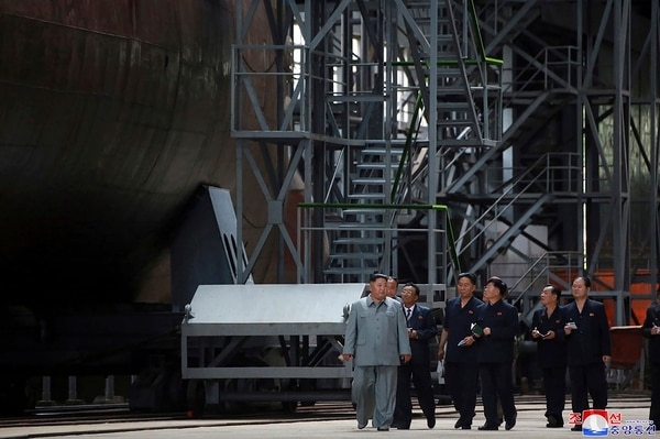 In this undated photo provided on Tuesday, July 23, 2019, North Korean leader Kim Jong Un, left, inspects a newly built submarine to be deployed soon, at an unknown location in North Korea. (Korean Central News Agency/Korea News Service via AP)