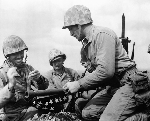 In this photo provided by the U.S. Marine Corps, three unidentified Marines of the 28th Regiment of the 5th Marine Division prepare to raise the smaller of two flags on Mount Suribachi, Iwo Jim, Feb. 23, 1945. The smaller flag was supplanted by a larger flag later that day. (Staff Sgt. Louis R. Lowery/Marine Corps via AP)