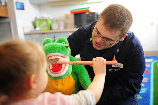 A Coast Guard health services technician teaches a 3-year-old child at the Child Development Center in Kodiak about the proper way to care for her teeth, in 2011. (Petty Officer 3rd Class Jonathan Lally/Coast Guard)