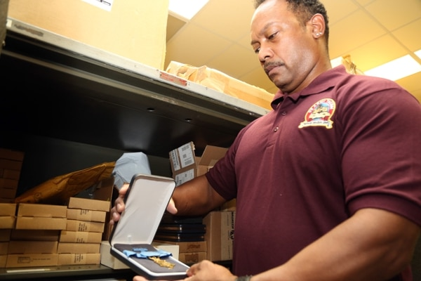 Shop Supervisor Ron Henry Jr. retrieves a prestigious Medal of Honor from a safe in the Veteran Medals Program warehouse.