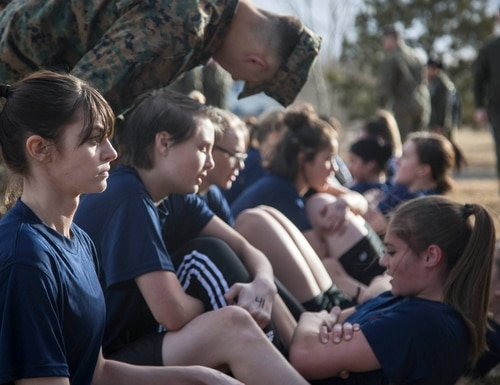 A female poolee waits after completing the two-minute timed crunches portion of the Initial Strength Test during a female pool function aboard Buckley Air Force Base in Aurora, CO, Feb. 11, 2017. The female pool function served to prepare females in the Marine Corps Delayed Entry Program for the rigors of Marine Corps recruit training.