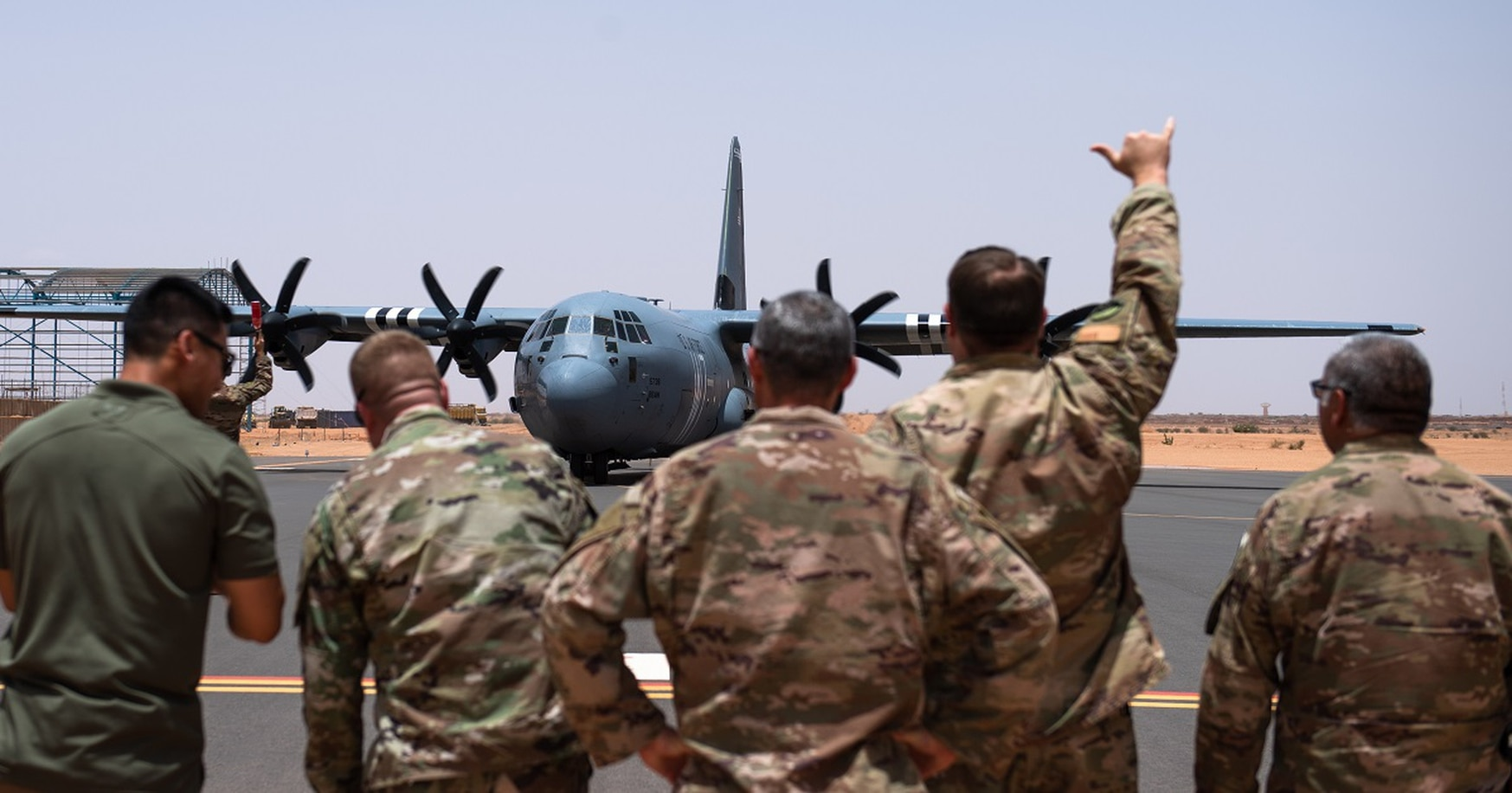 Airmen assigned to the 409th Air Expeditionary Group watch as a C-130J Super Hercules taxis in at Air Base 201 in Agadez, Niger, Aug. 3. The C-130 landing marked the next step in airfield evaluations by starting Visual Flight Rules operations at the base. (Staff Sgt. Devin Boyer/Air Force)