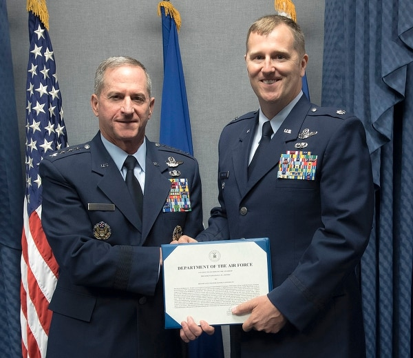 Lt. Col Daniel Finnegan, right, receives the Koren Kolligian Trophy certificate from Air Force Chief of Staff Gen. Dave Goldfein in the Pentagon on June 25. (Wayne A. Clark/Air Force)