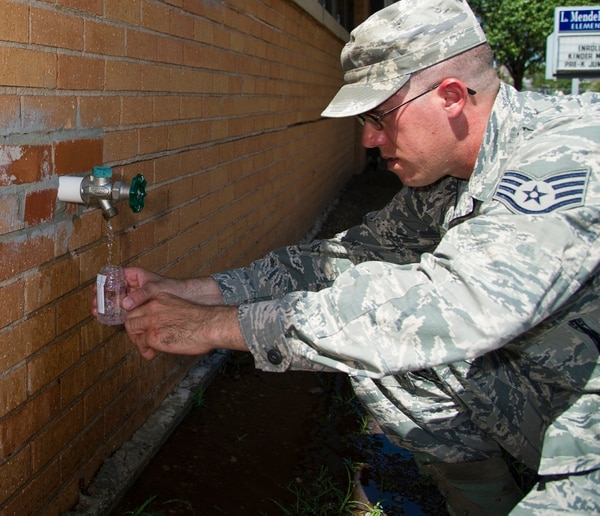 ALTUS AIR FORCE BASE, Okla. -- Staff Sgt. Marshall Varrato, 97th Medical Operations Squadron bioenvironmental engineering NCO in charge of readiness and training, collects a water sample during a routine water sampling at Rivers Elementary School. Members of the 97th MDOS bioenvironmental engineering flight conduct water samplings twice a month. The samples are collected and then delivered to a lab in Elk City, Okla. where they are tested for contaminants. (U.S. Air Force photo by Senior Airman Kenneth W. Norman / Released)