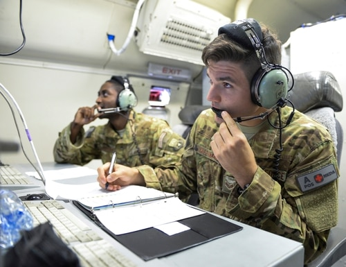 U.S. Air Force Senior Airmen Mehmet Yasdiman, foreground, and William Pryor study their computer monitors during a mission aboard an E-8C Joint Surveillance Target Attack Radar System aircraft out of Al Udeid, Air Base, Qatar, on July 27, 2017. (Tech. Sgt. Bradly A. Schneider/U.S. Air National Guard)
