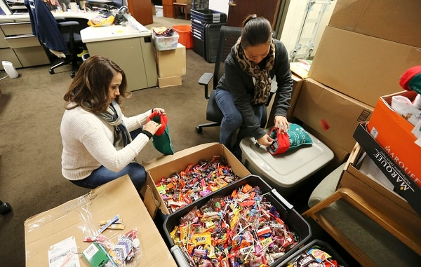 In this Nov. 13, 2018, photo, Soldiers Angels' staffers Sheila Williams, right, and Vanessa Vinton, left, puts handfuls of candy into stockings, which will be sent out to members of the armed services. (Kin Man Hui/The San Antonio Express-News via AP)