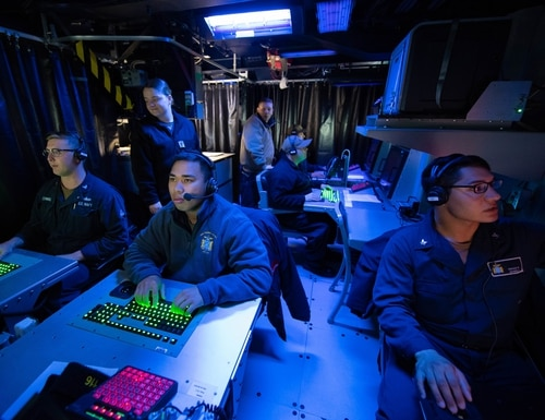 Operations specialists assigned to the Arleigh Burke destroyer Thomas Hudner conduct Tomahawk exercise procedures in the Command Information Center at a 2019 joint force exercise. It was the first demonstration of the Advanced Battle Management System, when operators across the Air Force, Army, Navy and industry tested multiple real-time data-sharing tools in a homeland defense-based scenario at Eglin Air Force Base, Florida. (MC3 Marianne Guemo/U.S. Navy)