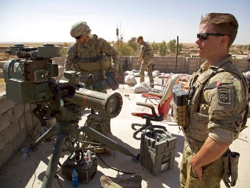 In this Aug. 20 photo, U.S. soldiers stand next to a guided-missile launcher a few miles from the frontline in the village of Abu Ghaddur, east of Tal Afar, Iraq. American troops have started to draw down from Iraq following Baghdad's declaration of victory over the Islamic State group last year, according to western contractors at a U.S.-led coalition base in Iraq. (Balint Szlanko/AP)