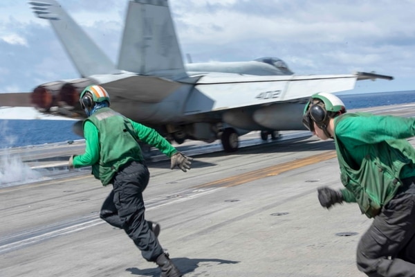 Sailors run to retrieve a holdback bar following the launch of an F/A-18E Super Hornet assigned to Strike Fighter Squadron 195 on board the aircraft carrier Ronald Reagan on Aug. 5 in the South China Sea. (Mass Communication Specialist 2nd Class Tyra M. Campbell/Navy)