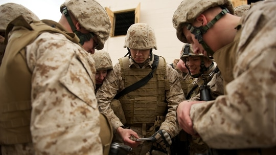 Marine Cpl. Terrence Nuss (center), a D Company, Anti-Terrorism Battalion squad leader, shares smartphone footage of his Marines maneuvering during training in urban operations April 21 at JBER's Baumeister City MOUT Complex. (U.S. Air Force photo/David Bedard)