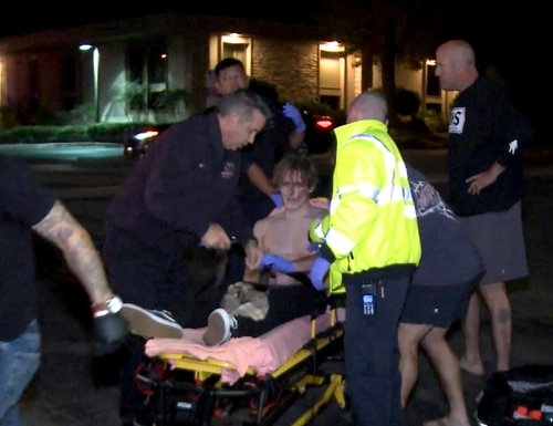 In this image taken from video a victim is treated near the scene of a shooting, Wednesday evening, Nov. 7, 2018, in Thousand Oaks, Calif. A hooded gunman dressed in black opened fire on a crowd at a country dance bar holding a weekly