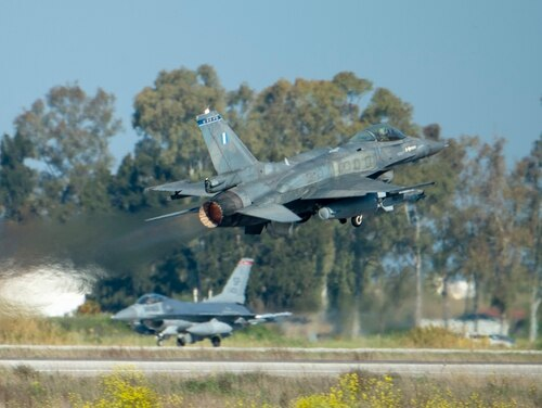 A Greek air force F-16 takes off while a U.S. Air Force F-16 taxis during exercise Iniohos 2019 at Andravida Air Base, Greece, April 2. (Airman 1st Class Branden Rae/Air Force)
