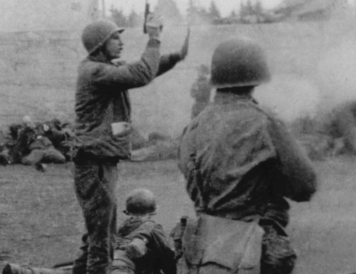 Army Lt. Col. Felix Sparks orders his troops to stop firing on German SS soldiers at Dachau concentration camp. (National Archives)