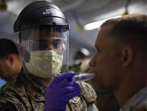Hospital Corpsman 2nd Class James Mckenzie takes the temperature of a Marine on Marine Corps Air Station Cherry Point, N.C., on March 31, 2020. (Lance Cpl. Scott Jenkins/Marine Corps)