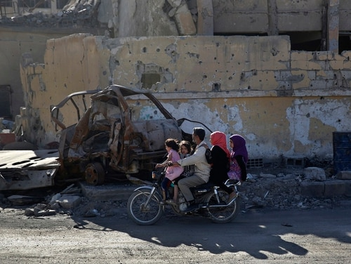 A family rides a motorcycle on a street that was damaged during fighting between U.S.-backed Syrian Democratic Forces fighters and Islamic State militants, in Raqqa, Syria on April 5, 2018. U.S. leaders are weighing a military strike against the Syrian regime for a chemical weapons attack against civilians in Douma last week. (Hussein Malla/AP)