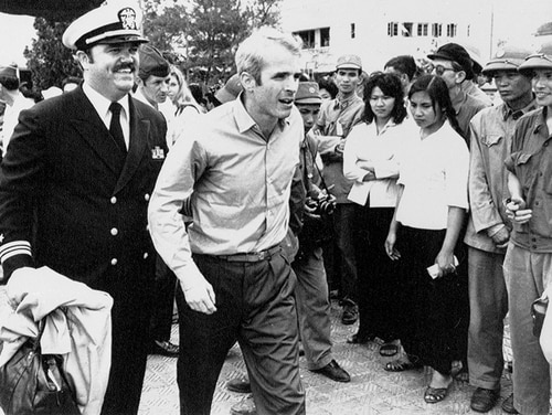 In this March 14, 1973, file photo, U.S. Navy Lt. Cmdr. John McCain, center, is escorted by Lt. Cmdr. Jay Coupe Jr., to Hanoi, Vietnam's Gia Lam Airport, after McCain was released from captivity. (Horst Faas/AP)