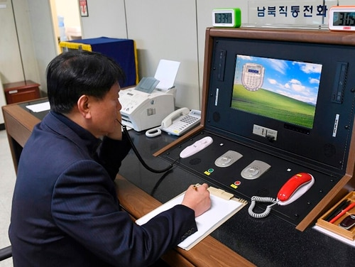 In this Jan. 3, 2018, file photo, a South Korean government official communicates with a North Korean officer during a phone call on the dedicated communications hotline at the border village of Panmunjom in Paju, South Korea. (South Korea Unification Ministry/Yonhap via AP)