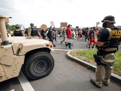 DC National Guard soldiers and other law enforcement personnel watch as demonstrators protest Saturday, June 6, 2020, along Independence Avenue in Washington, over the death of George Floyd, a black man who was in police custody in Minneapolis. Floyd died after being restrained by Minneapolis police officers. (Alex Brandon/AP)