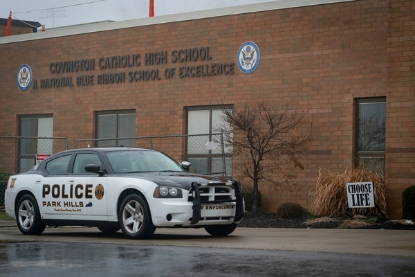 A police car sits in front of Covington Catholic High School in Park Hills, Ky., Saturday, Jan 19, 2019. A diocese in Kentucky apologized Saturday after videos emerged showing students from the Catholic boys' high school mocking Native Americans outside the Lincoln Memorial on Friday after a rally in Washington. (AP Photo/Bryan Woolston)