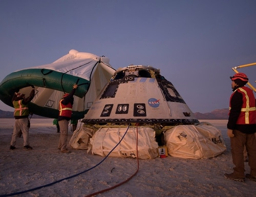 Boeing, NASA, and U.S. Army personnel work around the Boeing Starliner spacecraft shortly after it landed in White Sands, N.M., Sunday, Dec. 22, 2019.(Bill Ingalls/NASA via AP)