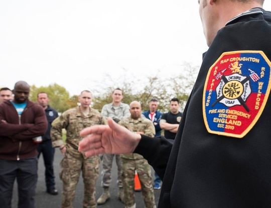 Mr. Tom Berrisford, right, fire inspector with the 422nd Civil Engineer Squadron, instructs a group of Firefighter Challenge contestants at RAF Croughton, England, on Oct. 5, 2018. (Tech. Sgt. Brian Kimball/Air Force)