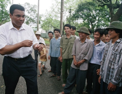 Muhammad Ali, left, assumes his former fighting stance while joking around with Vietnamese people on the path outside of Ho Chi Minh?s former home in Hanoi, Vietnam on Wednesday, May 11, 1994. Ali visited the families of American and Vietnamese servicemen still missing from the war, nearly three decades after he was convicted of draft evasion for refusing to fight on the battlefields. (AP Photo/Lois Raimondo)