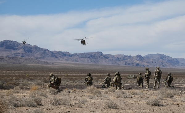 Special Forces soldiers and Air Force members watch as two UH-60 Black Hawk helicopters land on a designated landing zone Aug. 30, 2018, after executing a combat training exercise at the Nevada Test and Training Range in Nevada. (Sgt. Connor Mendez/Army)