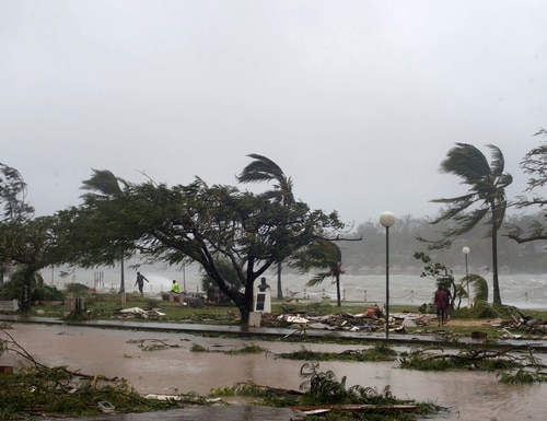 In this image provided by UNICEF Pacific, people walk along the shore where debris is scattered in Port Vila, Vanuatu, Saturday, March 14, 2015, in the aftermath of Cyclone Pam. Winds from the extremely powerful cyclone that blew through the Pacific's Vanuatu archipelago are beginning to subside, revealing widespread destruction. (AP Photo/UNICEF Pacific, Humans of Vanuatu) EDITORIAL USE ONLY, NO SALES