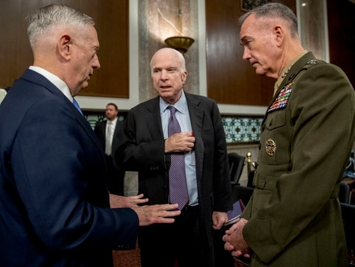 Defense Secretary Jim Mattis, left, and Joint Chiefs Chairman Gen. Joseph Dunford, right, speak with Arizona Sen. John McCain as they arrive to testify on Afghanistan before the Senate Armed Services Committee Oct. 3. (Andrew Harnik/AP)
