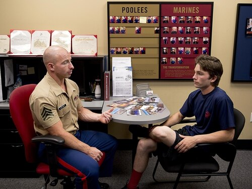 Sgt. Cody Leifheit, a Marine recruiter in Lewiston, Idaho, answers enlistee Brandon Roberts' questions about the Marine Corps at his recruiting office (Sgt. Reece Lodder/Marine Corps).
