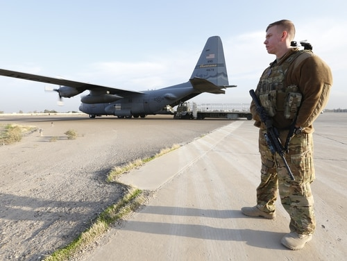 Tech. Sgt. Joseph Cull, a FAST, or Fly-Away Security Team, airman, guards a C-130H from the 120th Airlift Wing of the Montana Air National Guard while it is unloaded on the runway at Camp Taji, Iraq, on Jan. 10, 2017. (Stephen Losey / Air Force Times)