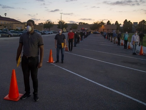 New recruits with Echo Company, 2nd Recruit training Battalion, are screened after arriving at Marine Corps Recruit Depot, San Diego, April 13, 2020. (Marine Corps)