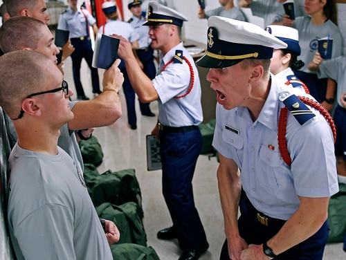 In this July 1, 2019, file photo, Whisky 2 company Cadre Jacob Denns, right, shouts instructions to swab Nicolas Fisher, left, of Pelham, N.H., on the first day of a seven-week indoctrination to military academy life for the Class of 2023 at the U.S. Coast Guard Academy in New London, Conn. (Sean D. Elliot/The Day via AP, File)