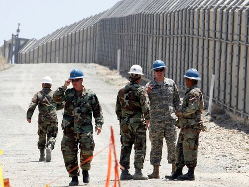 In this June 21, 2006, file photo, members of the California National Guard work next to the U.S.-Mexico border fence near the San Ysidro Port of Entry in San Diego. President Donald Trump said April 3, 2018, he wants to use the military to secure the U.S.-Mexico border until his promised border wall is built. (Denis Poroy/AP)