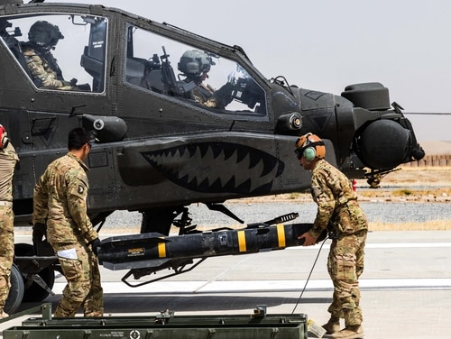 Army AH-64E Apache pilots assigned to 16th Combat Aviation Brigade, 7th Infantry Division prepare to depart for a mission as soldiers load an AGM-114 Hellfire missile onto the helicopter in Kunduz, Afghanistan in 2017. (Capt. Brian Harris/Army)