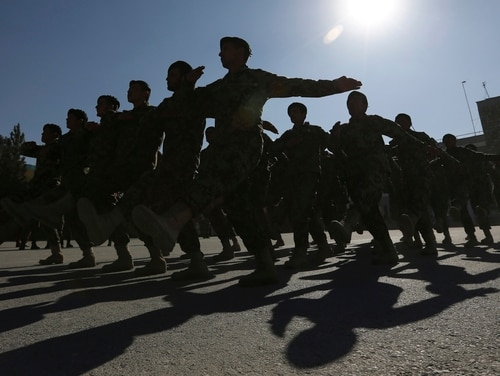 FILE - In this file photo taken Sunday, Nov. 23, 2014, new members of the Afghan National Army march during their graduation ceremony at the Afghan Military Academy in Kabul, Afghanistan. With U.S.-led forces shifting to a supporting role at the end of December, Afghanistan will have to chart its own course after the country's bloodiest year since the 2001 invasion, a year which saw record casualties among Afghan civilians and security forces alike. (AP Photo/Rahmat Gul, File)