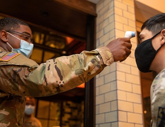Pfc. Caleb Brisard takes a soldier's temperature at the entrance of a local New York City hotel in support of the Department of Defense COVID-19 response, May 8, 2020. (Spc. Genesis Miranda/Army)