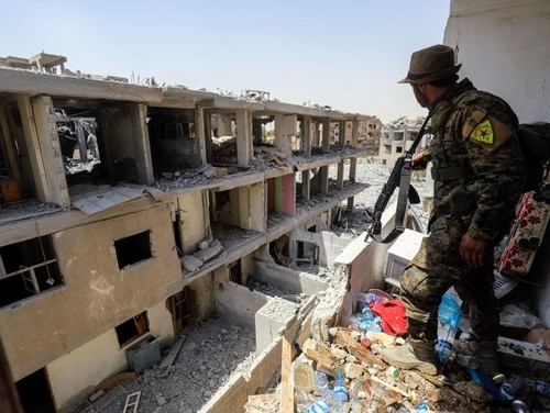 A member of the Kurdish People's Protection Units moves through destroyed buildings in Raqqa July 2. (Delil Souleiman/AFP/Getty Images)