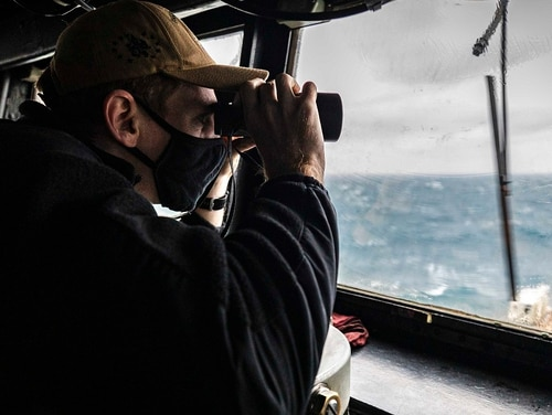 Ensign Grayson Sigler scans the horizon while standing watch as the guided-missile destroyer John S. McCain conducts freedom of navigation operations in the Taiwan Strait Wednesday. The destroyer Curtis Wilbur also transited the strait. (MC2 Markus Castaneda/Navy via AP)