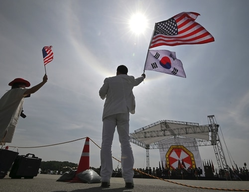 A man and a woman wave flags during a ceremony to commemorate the 75th anniversary of the Eighth U.S. Army at Camp Humphreys in Pyeongtaek on June 8, 2019. (Jung Yeon-je/AFP via Getty Images)