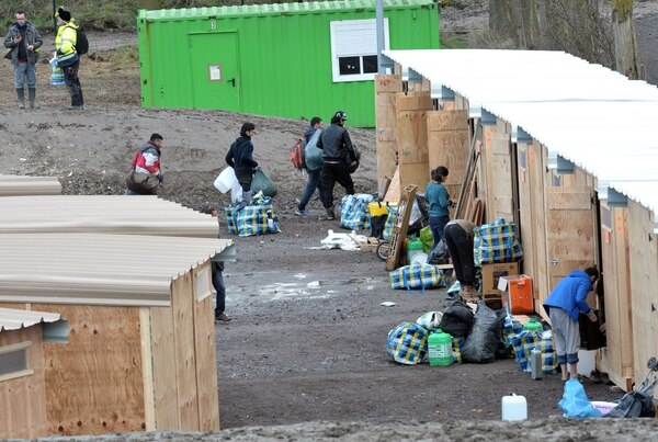 Migrants and refugees arrive in the first international-standard refugee camp on March 7, 2016 in Grande-Synthe, northern France. France opened its first international-standard refugee camp in the teeth of official opposition on March 7 while demolition continued at the nearby Calais