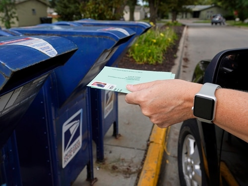 In this Aug. 18, 2020, file photo, a person drops applications for mail-in-ballots into a mailbox in Omaha, Neb. (Nati Harnik/AP)