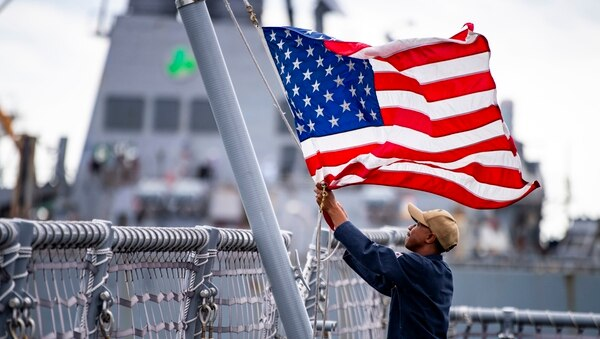 A sailor assigned to the littoral combat ship Billings lowers the flag as the ship got underway from Naval Station Mayport on Aug. 30. (Mass Communication Specialist 3rd Class Nathan T. Beard/Navy)