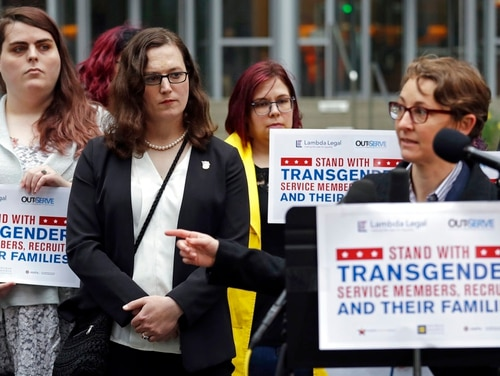 Plaintiff Cathrine Schmid, second from left, listens as attorney Natalie Nardecchia speaks in front of a federal courthouse following a hearing March 27, 2018, in Seattle. U.S. District Judge Marsha Pechman says she won't immediately consider President Donald Trump's new policy banning transgender people from serving in the military. (Elaine Thompson/AP)