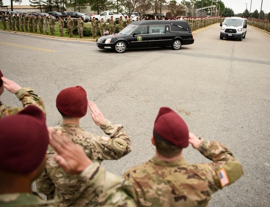 Soldiers salute as a hearse carrying the remains of Staff Sgt. Ian Paul McLaughlin drive by on Fort Bragg, N.C., on Saturday, Jan. 18, 2020. McLaughlin was killed Jan. 11 in Afghanistan. (Andrew Craft /The Fayetteville Observer via AP)