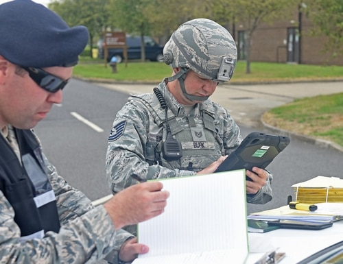 Air Force Staff Sgt. Jeremiah Johnson, left, inspects a 100th Security Forces Squadron patrolman as he references his checklist as the on-scene commander during a mission assurance exercise at RAF Mildenhall, England, in August 2018. Johnson died at his off-base home Saturday. (Airman 1st Class Brandon Esau/Air Force)