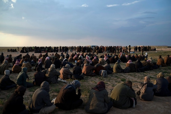 In this Feb. 22, 2019 file photo, men, foreground, women and children wait to be screened by U.S.-backed Syrian Democratic Forces fighters after being evacuated out of the last territory held by Islamic State militants, near Baghouz, Syria. (Felipe Dana/AP)